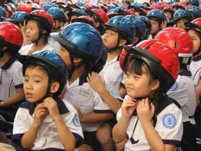 Các em học sinh đang đội mũ bảo hiểm