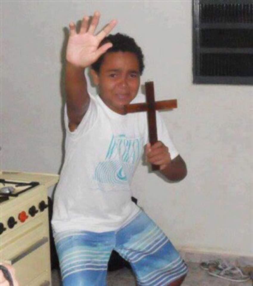 Cậu bé da đen tay cầm thánh giá