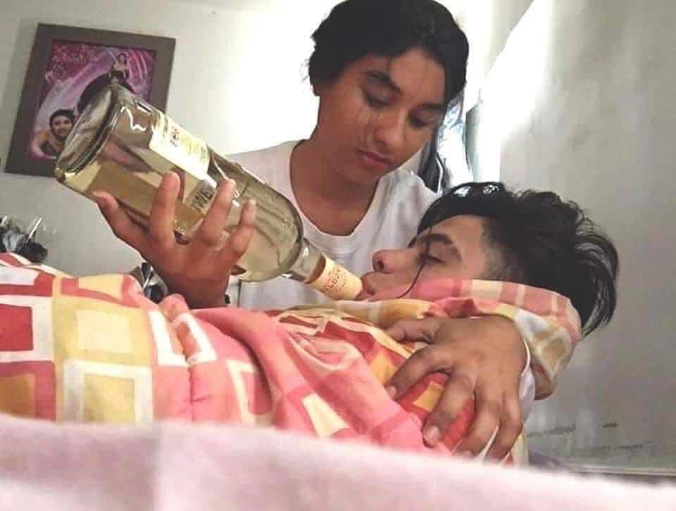 Cô gái chăm sóc chàng trai bị ốm với chai rượu