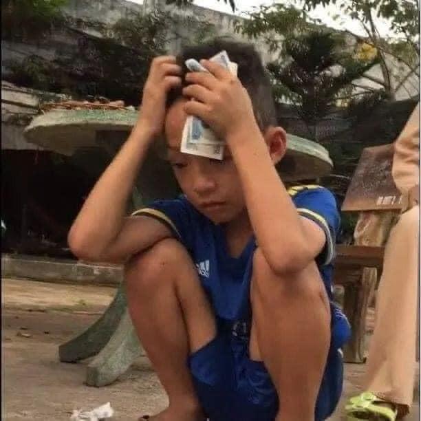 Cậu bé cầm tiền ôm đầu buồn bã