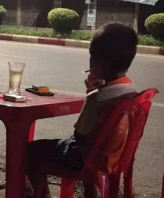 Thằng bé ngồi ghế nhựa hút thuốc như đang có nhiều tâm sự