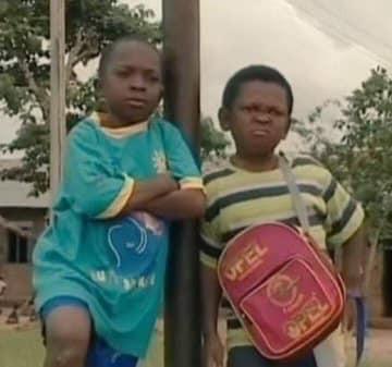 2 cậu bé da đen tựa cột nhìn khó hiểu