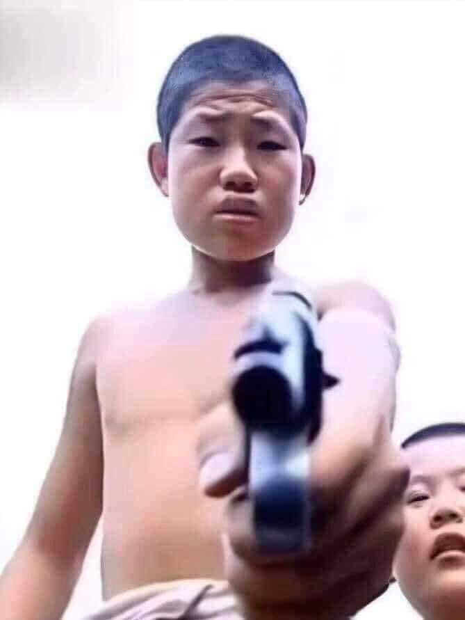Thằng bé cởi trần cầm súng chỉ vào màn hình