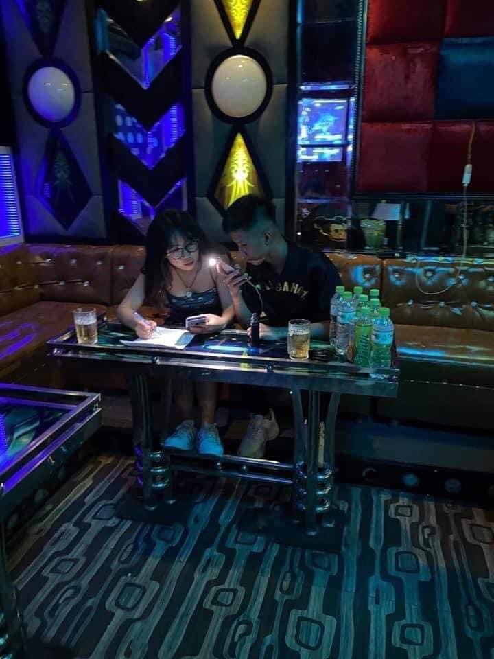 Đôi học sinh nam nữ gái xinh học bài trong quán karaoke