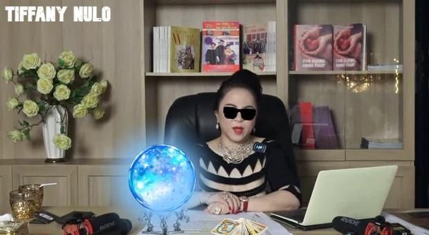Nhà tiên tri Phương Hằng ngồi ở bàn làm việc đeo kính râm với quả cầu tiên tri trên bàn